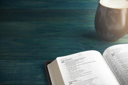 Foto de Holy Bible on a Blue Wooden Table Out for Studying - Imagen libre de derechos