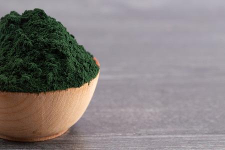 Foto de A Bowl of Spirulina Powder on a Wooden Table - Imagen libre de derechos