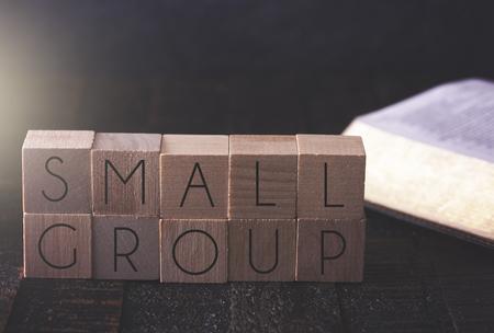 Foto de Small Group Spelled in Block Letters on a Wooden Table with a Bible - Imagen libre de derechos