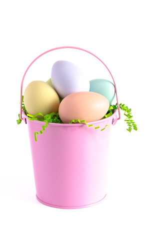 Photo for A Pink Easter Basket Filled with Decorated Eggs Isolated on a White Background - Royalty Free Image