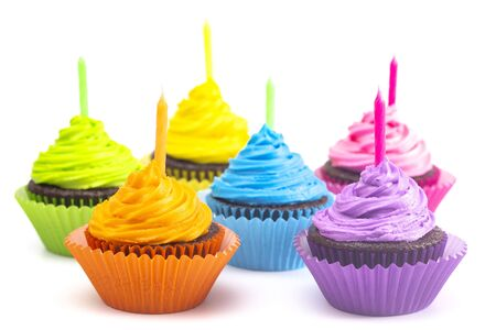 Photo pour Rainbow Colored Frosted Chocolate Cupcakes Isolated on a White Background - image libre de droit