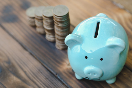 Blue piggy bank, Money growth on old wooden floor. ideas about saving money for future use - business success concept.