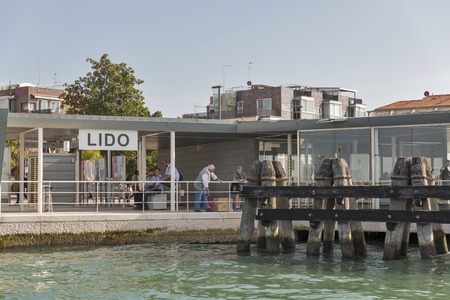 LIDO, ITALY - SEPTEMBER 23, 2016: Unrecognized people on Lido water bus vaporetto station. Lido is an island known for its 11 km long sandbar. Venice Film Festival takes place here every September.