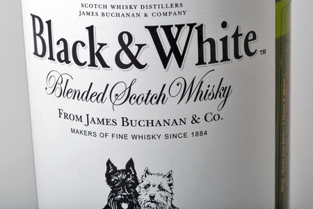 KIEV, UKRAINE - APRIL 17, 2016: Black and White blended Scotch Whisky bottle label closeup. It was originally produced by London James Buchanan Co Ltd. Black and White brand is now owned by Diageo.