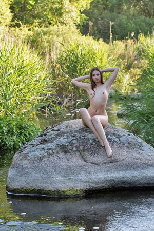 Beautiful young girl naked sits on big river stone at sunny morning