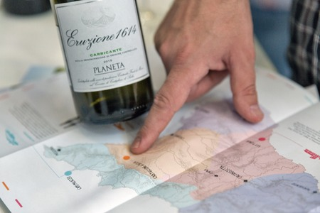 KIEV, UKRAINE - JUNE 02, 2018: Male finger indicates the place of growing Planeta Italian wine grapes on the map at Kyiv Wine Festival. 77 winemakers from around the world took part in big festival.