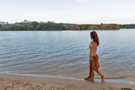Foto de young caucasian beautiful naked Amazon woman walk along river beach at sunset - Imagen libre de derechos