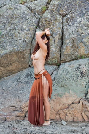 Photo for young caucasian beautiful naked Amazon woman stands in front of rocks on sand beach. - Royalty Free Image