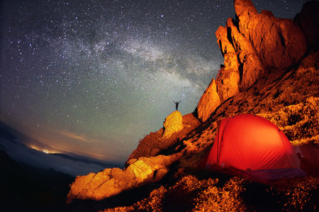 Tent and the Milky Way. Artistic lighting unreal mountain scenery while rock climbing in the wild mountains provides a unique fantastic effect unearthly planets with fabulous landscapes of Mars