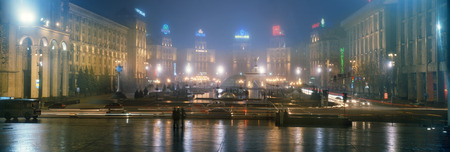 Kyiv, Ukraine - November 10, 2008: New Year in the capital of Ukraine - fog, rain, snow, mist in the air. Rare citizens going about their business, ancient buildings of Soviet architecture burn advertisement on sky background
