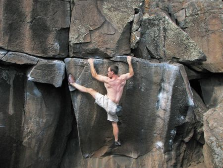 a man rock climbing without a rope stretches to reach a foothold