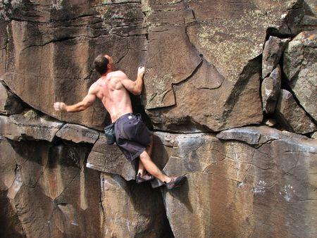 a man rock climbs on a vertical basalt wall without a rope