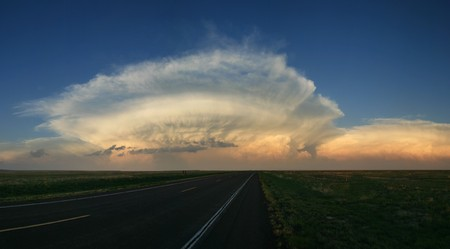 storm cell anvil head clouds above the great plains horizon just before sunsetの写真素材