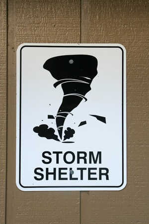 black and white tornado storm shelter sign on a brown wooden wall