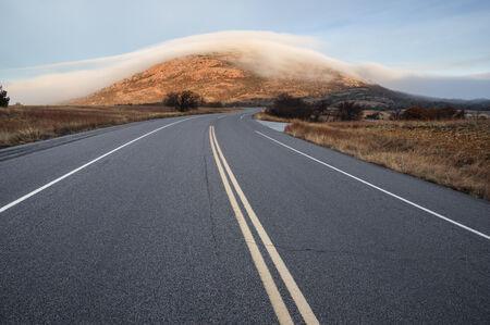 Highway 49 leads towards Mount Scott covered in fog in the Wichita Wildlife Refuge