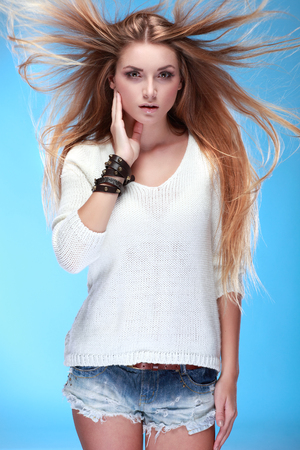 A photo of beautiful girl is in fashion style ,on a blue background, vintag