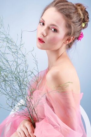 Photo pour Beautiful girl, isolated on a blue background with varicoloured flowers, emotions, cosmetics - image libre de droit