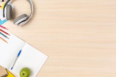 Photo for Wooden desk workplace top view nobody headphones notebook and stationery at the corner copy space - Royalty Free Image