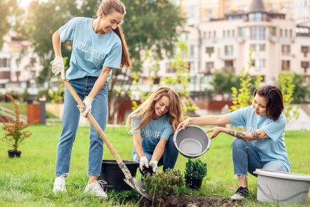 Photo for Volunteering. Young people volunteers outdoors planting trees digging ground pouring water cheerful - Royalty Free Image