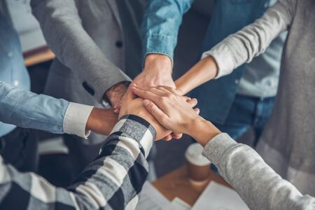 Photo pour Young business people working at office standing holding hands together top view close-up teamwork - image libre de droit