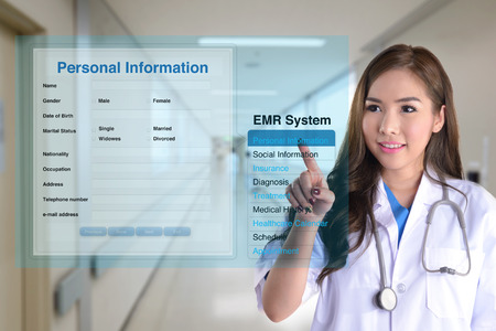Photo pour Female doctor using electronic medical record system to search patient information. - image libre de droit
