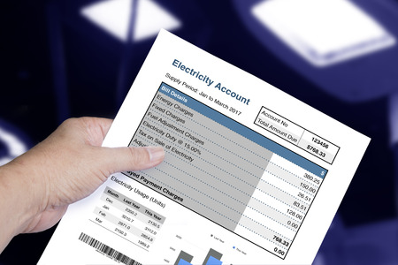 Electricity account bill in someone hand on dark and electric light background.