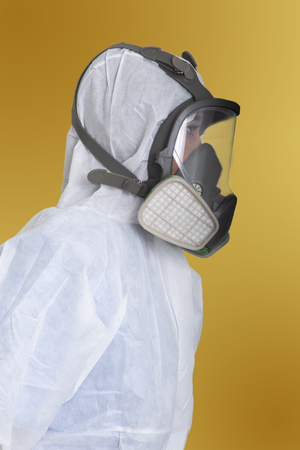 Foto de Side view of female worker in air pollution protection suit on yellow background. - Imagen libre de derechos