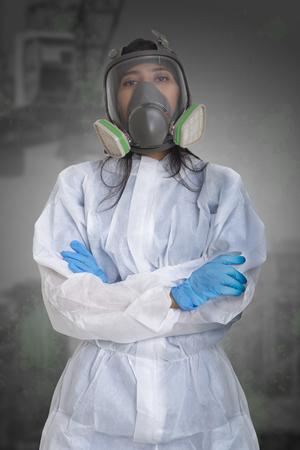 Foto de Female worker in dust protection suit standing with her arm crossed. - Imagen libre de derechos