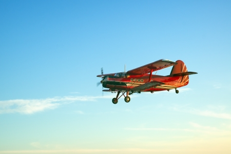 Red vintage airplane flying against blue sky