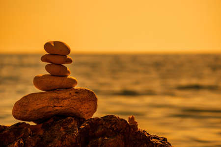 Photo pour Pyramid stones on the seashore on a sunny day on the blue sea background. Happy holidays. Pebble beach, calm sea, travel destination. Concept of happy vacation on the sea, meditation, spa, calmness. - image libre de droit