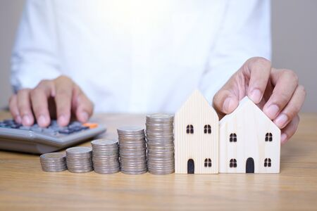 Photo pour Hand putting coins stacks near wooden house model and use calculator to calculate on the wooden table. Saving money for future investments and Planning to save money to buy a house. - image libre de droit