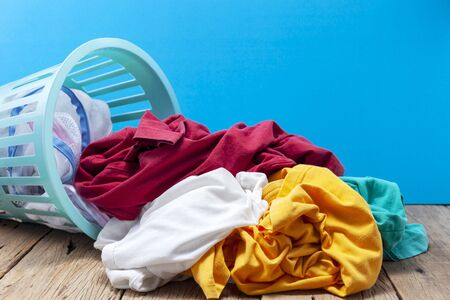 Photo pour Pile of dirty laundry in washing basket on wooden,blue background. - image libre de droit