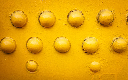yellow metal background with rivets
