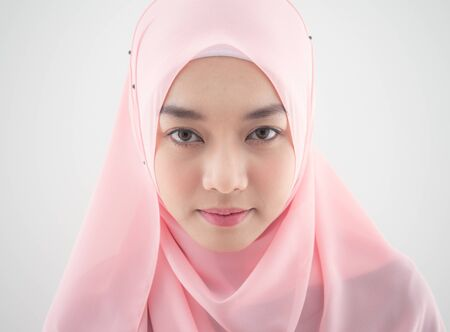 Photo pour Close up Portrait of a beautiful Muslim Asian woman in a pink hijab on white background. - image libre de droit