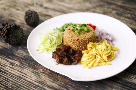 Asian food. Rice Seasoned With Shrimp Paste (Khaao Khlook Gabpi) on wooden background, Kao Cluk Ka Pi, Rice Mixed with Shrimp paste