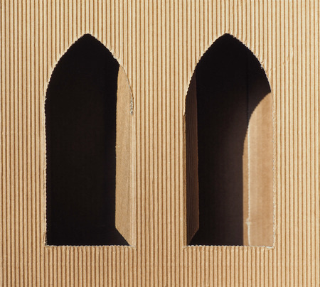 Brown corrugated cardboard with gothic window openings useful as a background
