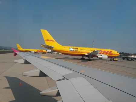 ORIO AL SERIO, BERGAMO, ITALY - CIRCA JULY 2014: DHL mailing company aircrafst parked at the airport with passenger shuttle