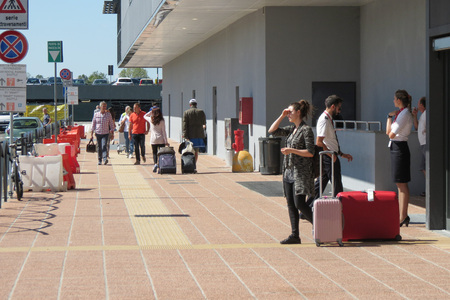 ORIO AL SERIO, BERGMAMO, ITALY - CIRCA SEPTEMBER 2015: Travellers with their trolley in front of the airport