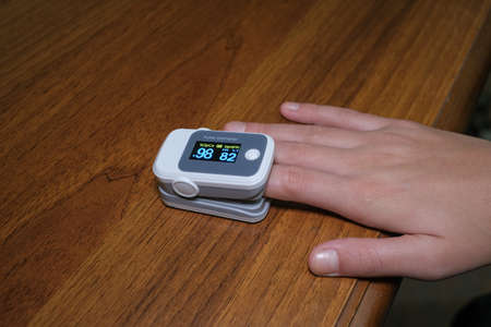 Photo pour Young woman using pulse oximeter to measure oxygen saturation in covid19 pandemic disease,medical home monitoring treatment - image libre de droit