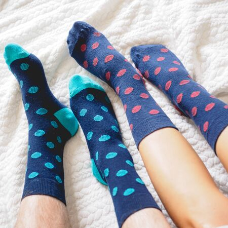 Foto de Young couple posing for a selfie feet wearing blue and white polka dotted socks. Square format. - Imagen libre de derechos
