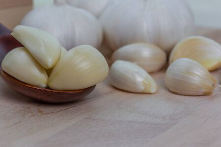 Foto für Peeled garlic slices are placed in a wooden spoon with the copying space. - Lizenzfreies Bild