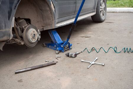 The car costs without a wheel on a jack during repair.