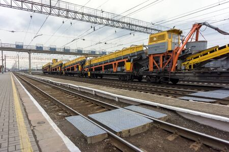Photo pour Freight train with industrial equipment stands on the tracks of a junction railway station with rails in the foreground. - image libre de droit