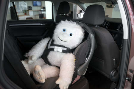 Photo pour The soft toy is located in the infant car seat, fastened with a dog safety belt, inside the car. - image libre de droit