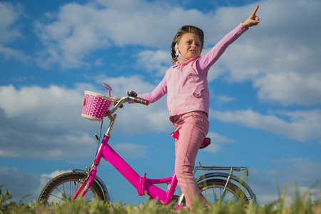 A girl in a pink helmet on a bicycle shows a finger something interesting to her parents