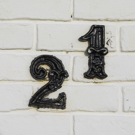 cast metal house number twenty-one. Separate black lettering on a white  painted brick wall.
