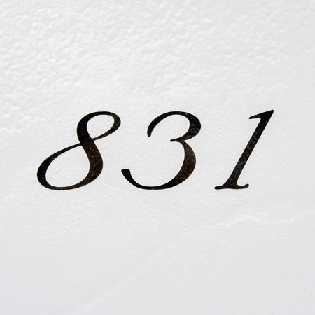 House number eight hundred and thirty one. Black lettering on a white wall