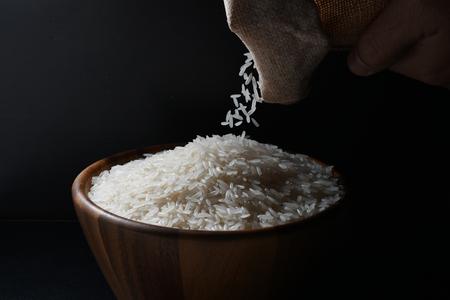 Photo pour Pouring jasmine rice into a wooden bowl on black background - image libre de droit