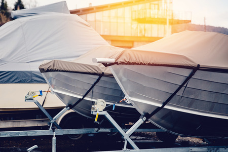Photo pour Row of boats in storage for the winter under the awning. Warehouse on the boat pier. Concept preparation for winter. - image libre de droit
