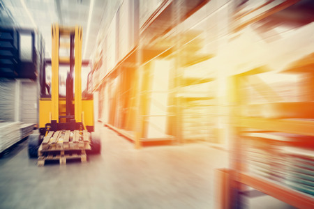 Photo pour Warehouse industrial premises for storing materials and wood, there is a forklift for containers. Concept logistics, transport. Motion blur effect. Bright sunlight. - image libre de droit